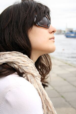 Woman in sunglasses on background of wall. She wearing in kerchief.  photo