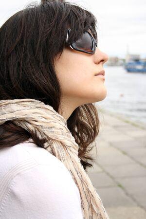 brune: Woman in sunglasses on background of wall. She wearing in kerchief.