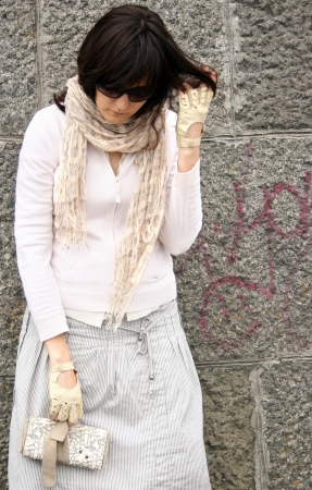 brune: Woman in sunglasses on background of wall. She wearing in scarf and gloves and hold clutch.