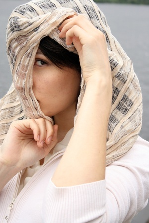 Woman in kerchief on her head looking sad. Arabic style portrait of a young beautiful girl. photo