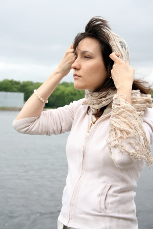 Woman in kerchief on her head looking sad. She stand near the waterside. photo