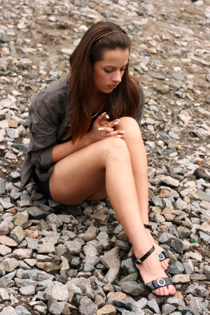 Thoughtful young woman sit on the ground photo