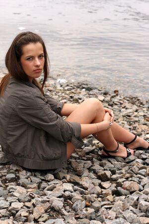 Thoughtful young woman sit near the waterside. Stock Photo - 16244230