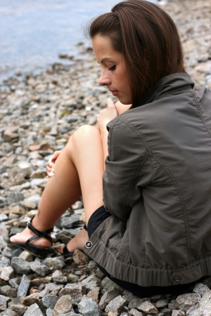 Thoughtful young woman sit near the waterside.