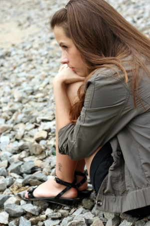 Thoughtful young woman sit on the ground and looking frontwards. photo