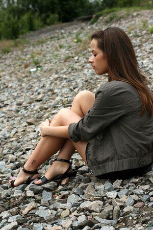 Thoughtful young woman sit on the ground. photo