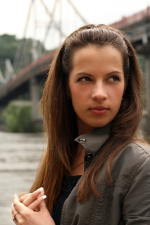 Serious woman near the brige in autumn time. photo