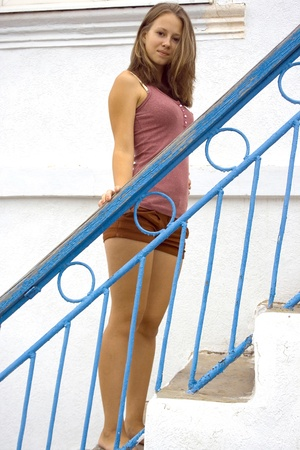 Barefoot young blonde woman on stairs. She looking at the camera.