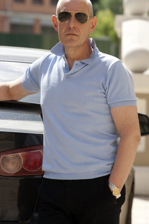 Middle aged caucasian man standing near his car. photo