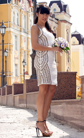 heelpiece: A lovely bride on city . She hold her bouquet and smile. Stock Photo