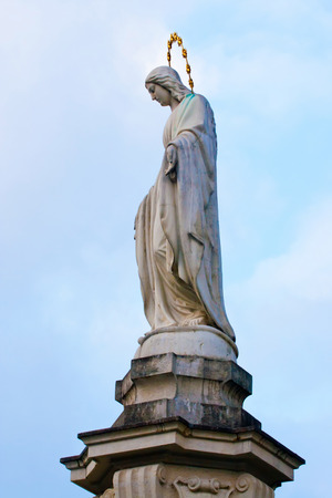 Statue of Mary praying in profile on background of blue sky.