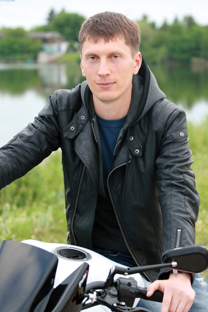 Young man standing on a motorcycle. Stock Photo
