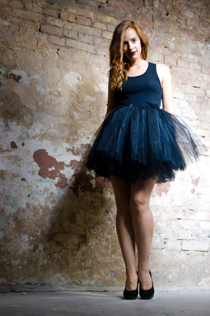 Beautiful woman with vinous lips. She dressed in black ballet skirt.