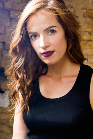 Beautiful woman with vinous lips. She dressed in black shirt. photo