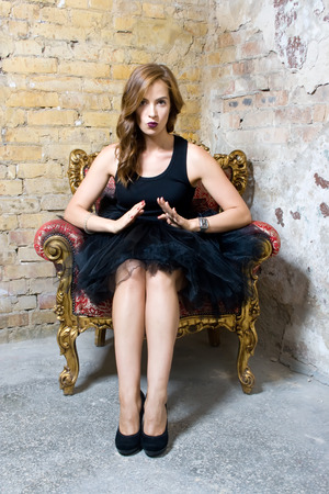 Beautiful woman dressed in black ballet skirt. She sits in a chair near brick wall