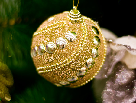 Golden New Year ball hanging on a Christmas tree