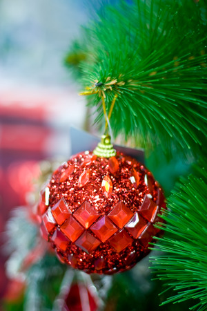Red New Year ball hanging on a Christmas tree. Stock Photo