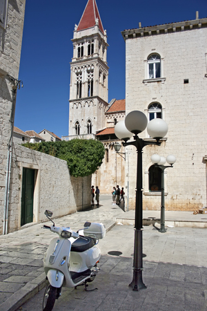 White motor scooter at the street of the city of Trogir, Croatia Stock Photo