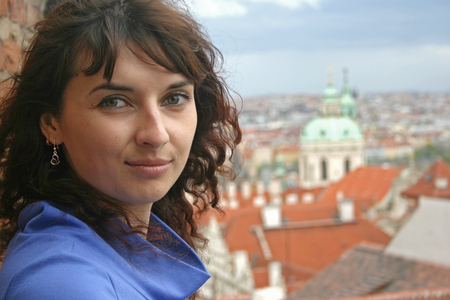 Beautiful curly brunette woman on an excursion in Prague, Czech Republic