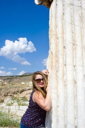 Beautiful blonde woman in sunglasses near greek column in Hierapolis, Turkey