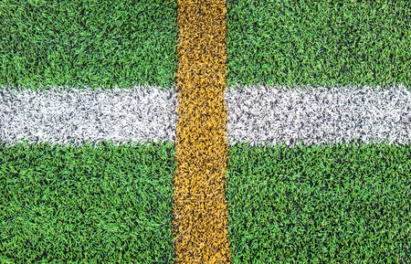 White and yellow line cross in soccer field photo