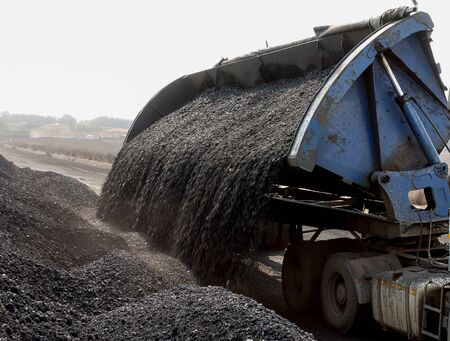 Truck dumping coal at railway siding for export