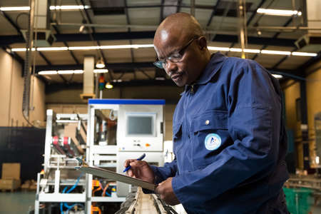 Johannesburg, South Africa - August 13, 2015: Black African male supervisor checking a clipboard on a packaging plant assembly line Editorial