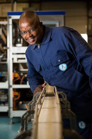 Johannesburg, South Africa - August 13, 2015: Black African male supervisor checking a machine on a packaging plant assembly line
