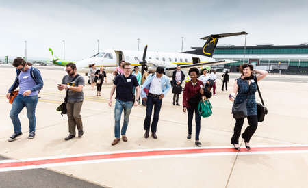Johannesburg, South Africa - November 27, 2014: Passengers disembarking a small charter propeller engine airplane at local airport