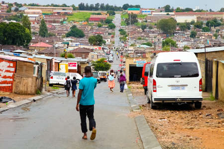 Johannesburg, South Africa - January 17, 2011: African people walking down a main road in Alexandra township, a formal and informal settlement