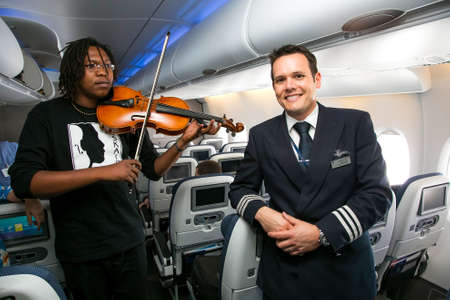 Johannesburg, South Africa - February 06, 2014: African Musician playing a violin on board a Airbus A380 Editorial
