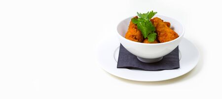 Fried Food in a white bowl on a white plate on a white background