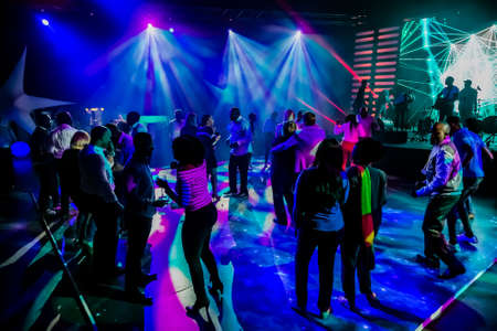 Johannesburg, South Africa - April 13, 2016: Group of people dancing on a dance floor in dark night club environment