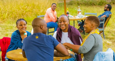 Johannesburg, South Africa, 05/09/2015,  Two African couples laughing together at The Winter Sculpture Fair at Nirox Sculpture Park