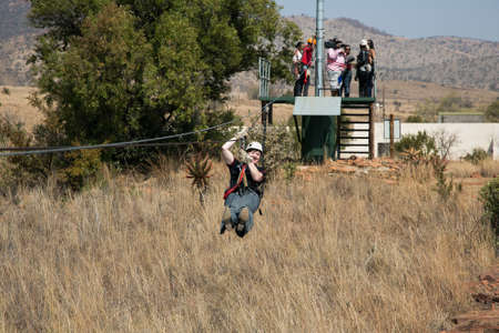 Johannesburg, South Africa - August 28 2013: Diverse Adults having fun on a Zip Line ride in the countryside Editorial