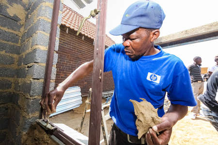 Soweto, South Africa - September 05, 2009: African builder installing windows on a Community Outreach program to build a small affordable house in local township