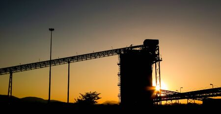 Silhouette of a mining silo and conveyor belts at sunset on a Palladium Platinum Mine