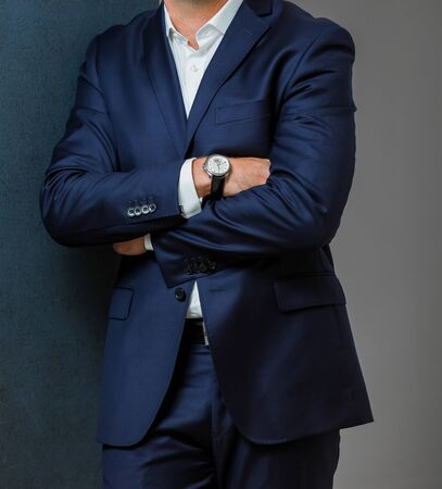 Close-up cropped Caucasian hands and arms of businessman in a suit with folded arms