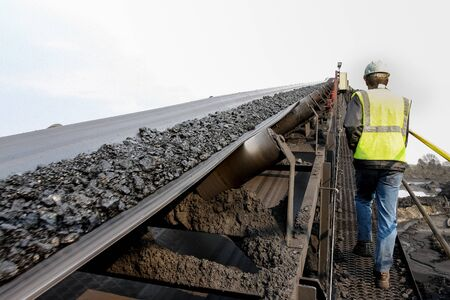 Man walking up a platform with a conveyor belt with coal ore on Stock Photo