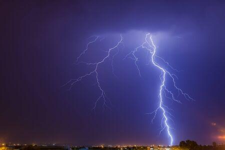 Blitzeinschlag von Wolke zu Boden über Johannesburg in der Nacht. In dieser Region Südafrikas gibt es jährliche Sommergewitter Standard-Bild