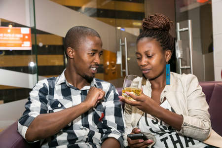 Johannesburg, South Africa - December 10 2014: Young African couple drinking Whiskey out of a tumbler glass in a cigar lounge