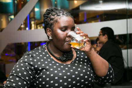 Johannesburg, South Africa - December 10 2014: Young African Woman drinking Whiskey out of a tumbler glass in a cigar lounge Redactioneel