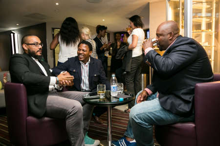 Johannesburg, South Africa - December 10 2014: Young African Men drinking Whiskey out of a tumbler glass in a cigar lounge
