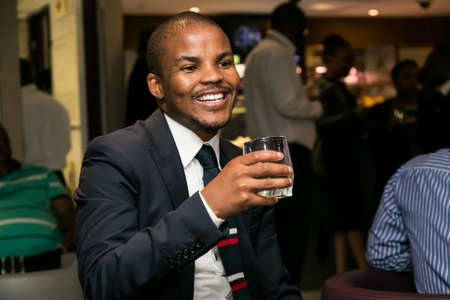 Johannesburg, South Africa - December 10 2014: Young African Man drinking Whiskey out of a tumbler glass in a cigar lounge