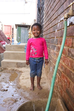 Soweto, South Africa - September 11, 2009: Little African Girl getting splashed by hosepipe water in a Soweto Township back yard Editorial