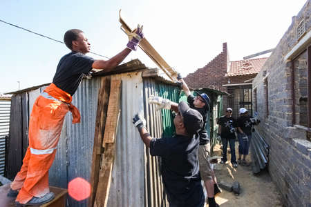 Soweto, South Africa - September 05, 2009: Community Outreach program helping to install metal roofing on a small affordable house in local township Éditoriale