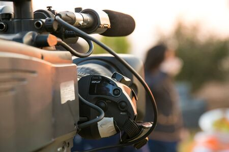 TV Camera and presenter host on a live news broadcast on location at sunrise