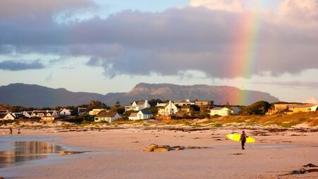 Cape Town, South Africa, July 11, 2008, A young surfer at sunset at Long Beach Noordhoek Cape Town with a beautiful rainbow in the background