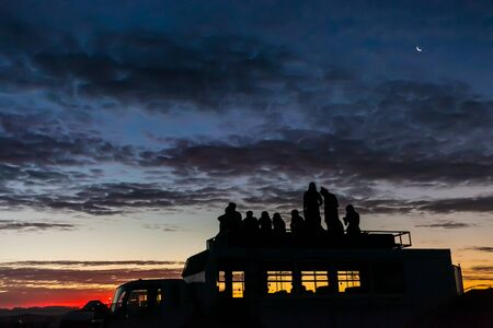 Silhouette of friends watching the sunset from the top of a tour bus