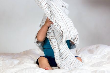 Small Caucasian boy playing under a striped blanket on white duvet bedding Stock Photo
